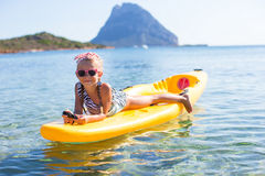 Adorable little girl kayaking in blue sea during Stock Photography