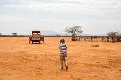 Little girl in Africa. Adorable little girl in Kenya safari walking towards open vehicle Stock Photo