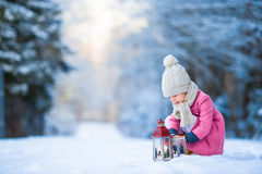 Adorable little girl with latern in frozen forest on Christmas at winter day Stock Image