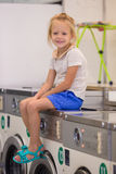 Adorable little girl in laundry room Royalty Free Stock Images