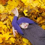 Adorable little girl laying on golden maple leaves Royalty Free Stock Photography