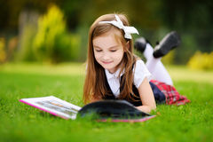 Adorable little girl laying on a grass reading a book Royalty Free Stock Photos