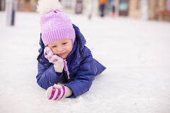Adorable little girl laying on skating rink after Stock Photos