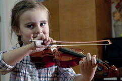 Adorable little girl learning violin playing royalty free stock photos