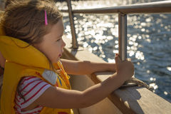 Adorable little girl in a life jacket traveling on boat Stock Photos
