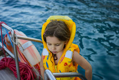 Adorable little girl in a life jacket traveling on boat Stock Image