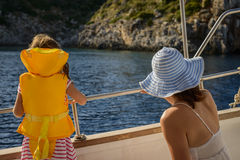Adorable little girl in a life jacket traveling on boat with her mother Stock Image