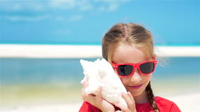 Adorable little girl listening a big seashell on white tropical beach. SLOW MOTION stock video