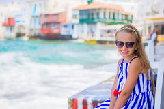 Adorable little girl at Little Venice the most popular tourist area on Mykonos island, Greece. Beautiful kid smile and Stock Image
