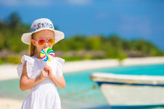 Adorable little girl with lollipop on tropical Royalty Free Stock Image