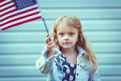 Adorable little girl with long curly blond hair holding american flag. And waving it. Independence Day, Flag Day concept. Vintage and retro colors. Instagram royalty free stock photography