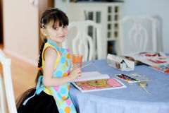 Adorable little girl with long dark hair draws Royalty Free Stock Photography