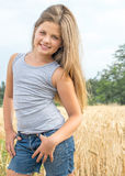 Adorable little girl with long hair posing in wheat field at a summer day. Portrait of a beautiful 8-year-old girl with long hair and green eyes in a golden Royalty Free Stock Photography
