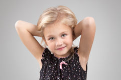 Adorable little girl looking at the camera. Adorable smiling little girl looking at the camera with his arms crossed behind his head close-up Royalty Free Stock Photo
