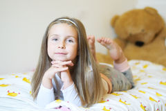 Adorable little girl looking at the camera with his arms crossed behind her head close-up. Adorable little girl looking at the camera with his arms crossed Royalty Free Stock Photography