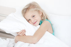 Adorable little girl looking at the camera. And hugging a pillow sitting on a bed on the background of a rough wall with texture Royalty Free Stock Image