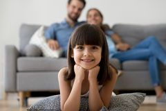 Adorable little girl looking at camera lying on warm floor. Relaxing with parents at home, smiling happy child posing playing in living room on family weekend stock photo
