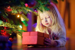 Adorable little girl looking for gifts under a Christmas tree Royalty Free Stock Photos