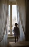 Adorable little girl looking out the window at Royalty Free Stock Image