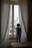 Adorable little girl looking out the window at Stock Photos