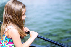 Adorable little girl looking at river on a beautiful summer day Stock Images