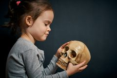 Adorable little girl is looking at the skull. On a black background royalty free stock photo