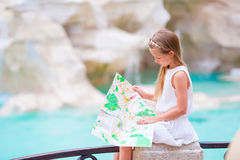 Adorable little girl looking at touristic map near Trevi Fountain, Rome, Italy. Happy toodler kid enjoy italian vacation Stock Photography