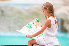 Adorable little girl looking at touristic map near Trevi Fountain, Rome, Italy. Happy toodler kid enjoy italian vacation Royalty Free Stock Photography