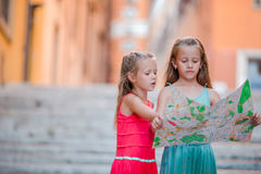 Adorable little girl looking at touristic map in roman streets in Italy. Happy toodler kids enjoy italian vacation Stock Photo