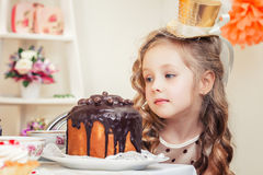 Adorable little girl looks thoughtfully at cake Stock Photo
