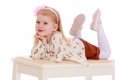 Adorable little girl lying on the banquette Stock Image