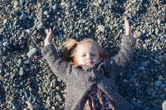Adorable Little girl lying on the beach in a Royalty Free Stock Photo