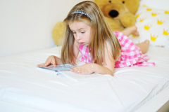 Adorable little girl lying on the bed and reading a book. At home Royalty Free Stock Photography