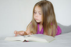 Adorable little girl lying on the bed and reading a book. Adorable little girl lying on the bed and reading interesting book Royalty Free Stock Photography