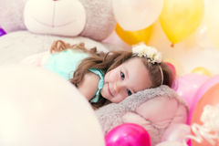 Adorable little girl lying on plush bear Stock Photo