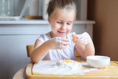 Adorable little girl making the dough for pasta. Adorable little girl making the dough for home pasta Royalty Free Stock Images