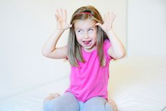 Adorable little girl making funny faces. At home Stock Photography