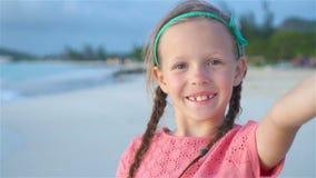 Adorable little girl taking selfie at tropical white beach. Slow motion. Adorable little girl making selfie at tropical white beach stock video