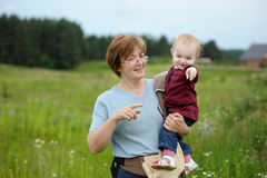 Adorable girl in a meadow with grandmother Stock Images
