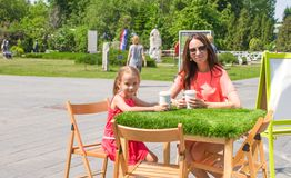 Adorable little girl and mom at outdoor cafe on Stock Photos
