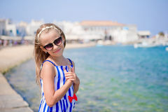 Adorable little girl at the most popular tourist area on Mykonos island, Greece. Beautiful kid smile and look in the Royalty Free Stock Image