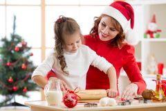 Adorable little girl and mother baking Christmas cookies royalty free stock photos