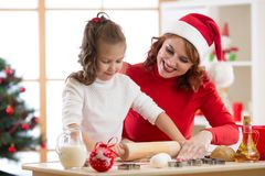 Adorable little girl and mother baking Christmas cookies stock images