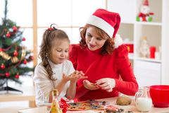 Adorable little girl and mother baking Christmas cookies stock image