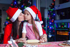 Adorable little girl with mother wearing santa Royalty Free Stock Photo