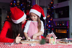 Adorable little girl with mother wearing santa Stock Photography