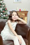 The little girl in the armchair by the Christmas tree. Adorable little girl new year`s eve on the backdrop of the Christmas tree sits on a leather armchair Stock Photos
