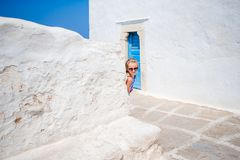 Adorable little girl at old street of typical greek traditional village. With white wall and blue doors Royalty Free Stock Photos