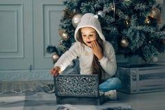 Happy child in Santa hat opening Christmas gift box stock image
