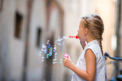 Adorable little girl outdoors blowing soap bubbles in european city. Portrait of caucasian kid enjoy summer vacation in Stock Images